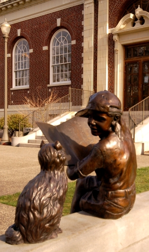 Statue of girl reading with cat in front of library
